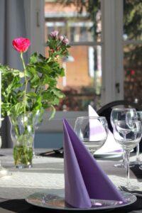 Græsted Kro - Havestuen med dækket bord og blomster